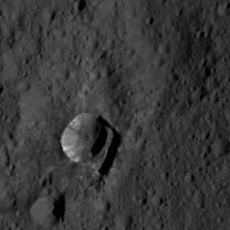 Oxo Crater, found to contain water ice. The streaky insides of this tiny crater look quite similar to the sides of Ahuna mons.